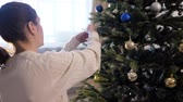 nice young woman in white sweater smiles and enjoys decorating artificial christmas tree branches close view Wideo