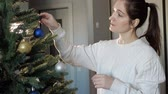 happy young lady with ponytail decorates artificial christmas tree with colorful and sparkling toy balls close view Wideo