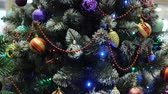 wonderful artificial christmas tree with bright sparkling decorations and shining garlands in shop extreme close view