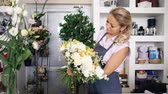 Working in flower shop. Professional florist is creating huge beautiful bouquet from fresh white roses, yellow lilys and green leaves. Seller on her workplace in uniform holding flower bunch.