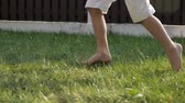 boso : little boy in white shorts with dirty bare feet runs fast on green grass on sunny day close low angle shot slow motion