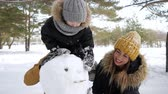 hóember : Happy family, mom, son and dad are making a snowman in winter park. Son is sitting on dads neck Stock mozgókép