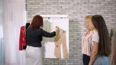 costuming : Seamstress teacher explain creating pattern of jacket showing details on mannequin. Tailor teaches students to sew clothes on cutting and sewing courses in workshop. Cutting and sewing courses. Stock Footage