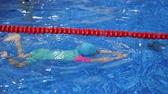 pływak : Child girl in goggles, swimsuit, cap and flippers is training swimming in pool. She swims in professional pool with transparent blue water. Child on swim lesson in sport school.