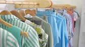 camera motes along wooden hangers with fashionable colorful summer clothes on rack in modern designer shop close view