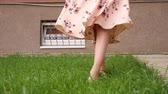 bare feet of slim lady in long pink summer dress walk along lush green grass lawn on warm day close low angle shot Wideo