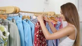 slim woman with loose fair hair holds wooden hanger and looks at blue summer dress near rack in shop close view