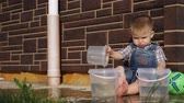 cute little boy with short fair hair sits near bricked house and pours water from plastic bucket close view slow motion