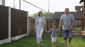 handsome father and pretty young mother hold happy little son hands and walk on green grass against fence slow motion