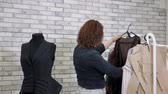 Working in tailoring business factory. Unrecognizable woman fashion designer in workshop chooses clothes hanging on hangers in atelier. She evaluates ready-to-run clothing models in production.