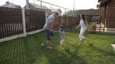 happy parents enjoy life and play football with active little boy on green garden lawn in hot sunny summer slow motion Wideo