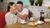 mensa : handsome young man kisses beautiful girlfriend during date at table served with tea and tasty cakes in cafe