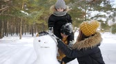 samen bouwen : Happy family, mom, son and dad are making a snowman in winter park. Son is sitting on dads neck Stockvideo
