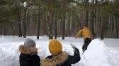hógolyó : Man is playing snowballs with his family in winter park. His wife and little son are hiding before snow wall. They are sitting back to camera. Stock mozgókép