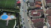 rotta : free street traffic between houses with brown roofs and park with swimming pool among plants upper panorama Filmati Stock