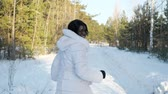 charming dark-skinned girl in white fur coat runs along park path covered with snow looking back backside view slow motion