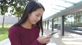 touchscreen : Woman using cellphone at outdoor Stock Footage