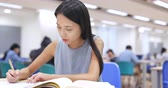 campus : Woman writing on her homework in library Stock Footage