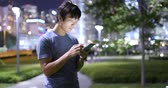 hk : Young man sending sms on cellphone at night Stock Footage