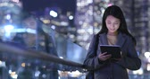 Business woman use of tablet computer at night
