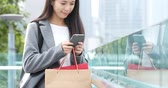 szár : Woman use of mobile phone and holding shopping bag