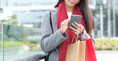 Woman holding shopping bag and use of mobile phone