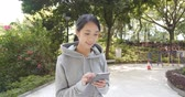 ウォーキング : Woman walking in park and use of mobile phone