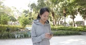 Woman use of mobile phone and walking in the park