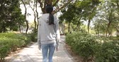 stabilizer : Woman walking in city park Stock Footage