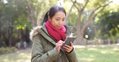 one use : Woman use of smart phone and wearing winter jacket at outdoor sunlight park Stock Footage