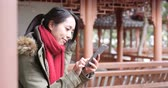 Woman looking at smart phone in Chinese garden