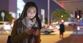 Young woman use of mobile phone in the city at night