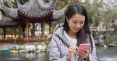 pavilion : Woman use of smart phone in chinese garden Stock Footage