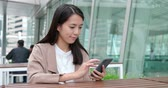 agency : Business woman using smart phone at outdoor cafe