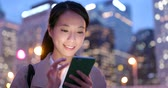 hk : Business woman use of smart phone in city at night Stock Footage
