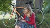 university : Pretty blonde woman relaxing on grass writing in a notebook. Bicycle and beautiful public park in the background. Stock Footage
