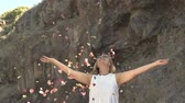 şehvetli : Beautiful blonde woman in white dress throwing up rose petals Stok Video