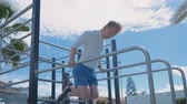 ginásio : Sports and Outdoors Training. Young man Training in Sportsground and Doing Pull Ups on Bars.