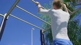 ginásio : Young man Training in Sportsground and Doing Pull Ups on Bars. Sports and Outdoors Training.
