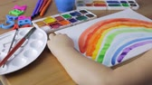 školka : Cute young girl painting a colored rainbow