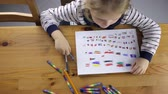 детский сад : Girl draws flags with colored pencils Стоковые видеозаписи