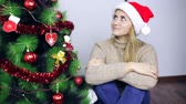 decorar : Girl is sitting at the Christmas tree and smiling Stock Footage