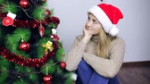 decorar : Woman sits by the Christmas tree and thinks Stock Footage
