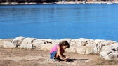loughing : Small girl throwing pebbles at the sea. Stock Footage