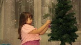 little : Little girl decorates the Christmas tree
