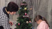 trees : mother and the daughter decorate a Christmas tree