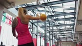 Kettlebell fitness, young female athlete doing strength exercises in the gym