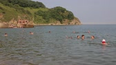 banho de sol : NAKHODKA, RUSSIA - JULY 29, 2015: Adults and children swim in the sea. on a sunny day. Locals love to relax, sunbathe, swim and dive in the sea bay near the city of Nakhodka. Vídeos