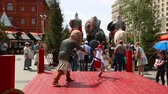 фехтование : MOSCOW - JUNE 12, 2016: Festivities in the Revolution square in central Moscow, dedicated to the Day of Russia June 12, 2016. Master of martial arts teaches child the rules of warfare with swords. Стоковые видеозаписи