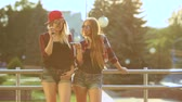 refill : Two women vaping outdoor. The evening sunset over the city. Toned image. Stock Footage